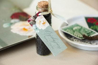 Podziękowania dla Gości w postaci buteleczek z herbatą, przywieszka na perłowym papierze w stylu boho z burgundowymi piwoniami