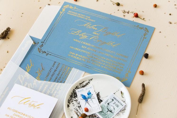 Eleganckie zaproszenia ślubne ze złoconą ramką. Zaproszenie ślubne w kolorze dusty blue z kaligrafinczą