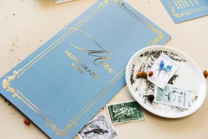 Menu weselne ze złoceniem w stylu Glamour w kolorze dusty blue z kaligrafinczą, złotą czcionką.