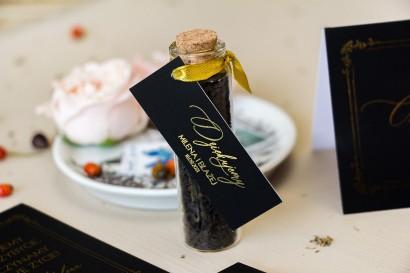 Prezenty dla Gości w postaci buteleczek z herbatą. Czarna Przywieszka w stylu glamour ze złotym tekstem oraz złotą ramką
