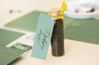 Prezenty dla Gości w postaci buteleczek z herbatą. Przywieszka z przewagą zieleni oraz złotą ramką