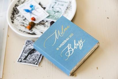 Prezenty dla gości weselnych w postaci mlecznej czekoladki, owijka w kolorze dusty blue z kaligrafinczą, złotą czcionką