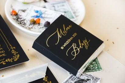 Prezenty dla gości weselnych w postaci mlecznej czekoladki, czarna owijka w stylu glamour ze złotym tekstem oraz złotą ramką