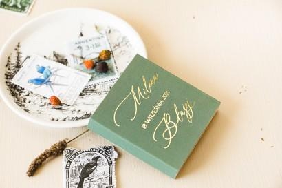 Prezenty dla gości weselnych w postaci mlecznej czekoladki, owijka z przewagą zieleni oraz złotą ramką