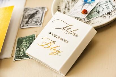 Prezenty dla gości weselnych w postaci mlecznej czekoladki, owijka w białym kolorze ze złoceniami