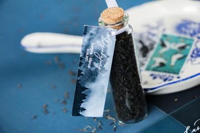 Podziękowania dla Gości w postaci buteleczek z herbatą. Buteleczka z herbatą liściastą, przywieszka z grafiką lasu