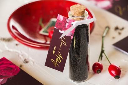 Podziękowania dla Gości w postaci buteleczek z herbatą. Burgundowa przywieszka ze złoceniami i kwiatowym motywem