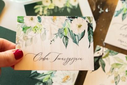 Winietki ślubne na drewnie w kolorze butelkowej zieleni z dodatkiem białych kwiatów i dekoracyjnych gałązek