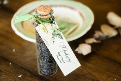 Podziękowania dla Gości w postaci buteleczek z herbatą, przywieszką z dodatkiem białych kwiatów i dekoracyjnych gałązek