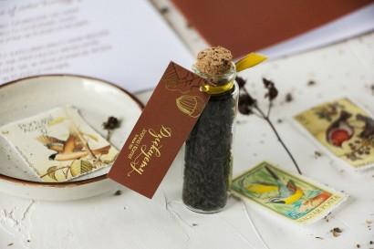 Prezenty dla Gości w postaci buteleczek z herbatą. Przywieszka ze złoceniami z motywem żołędzi