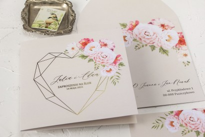 Kremowe zaproszenia ślubne ze złotym, geometrycznym sercem i bukietem pastelowych kwiatów