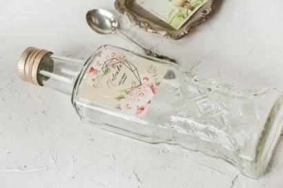 Ślubne Butelki na nalewki wraz z kremową etykietą ze złoceniami i z bukietem pastelowych kwiatów.
