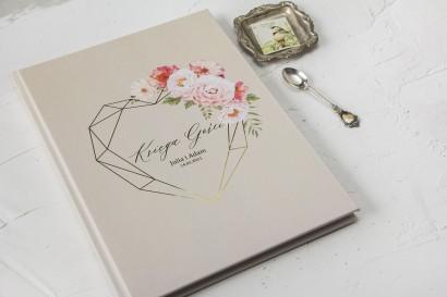 Kremowa Ślubna Księga Gości ze złoceniami i z bukietem pastelowych kwiatów.