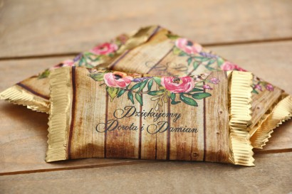 Czekoladki Rustykalne - dodatki ślubne - podziękowania dla Gości - różowe kwiaty na tle drewna