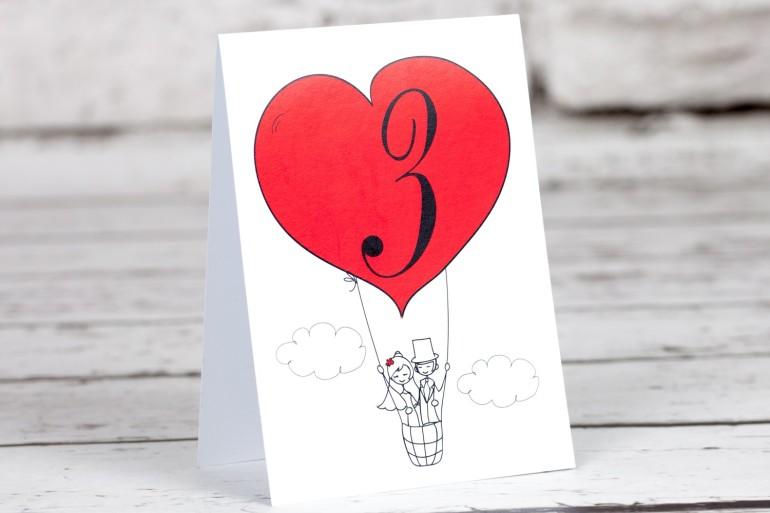 Numery stolików weselnych z kolekcji Bueno nr 1 - Rysunkowa para w czerwonym latającym balonie dryfującym w chmurach