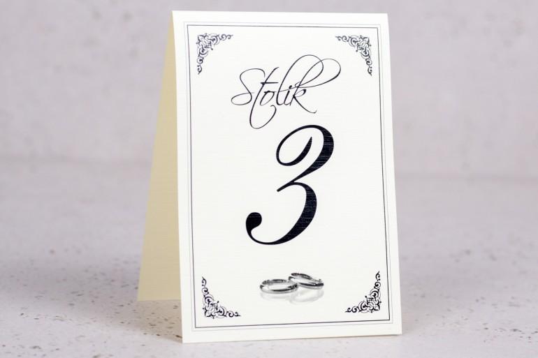 Ślubne numery stolików weselnych z kolekcji Arte nr 3 - Elegancki wzór z delikatną ramką i motywem obrączek - wersja ecru