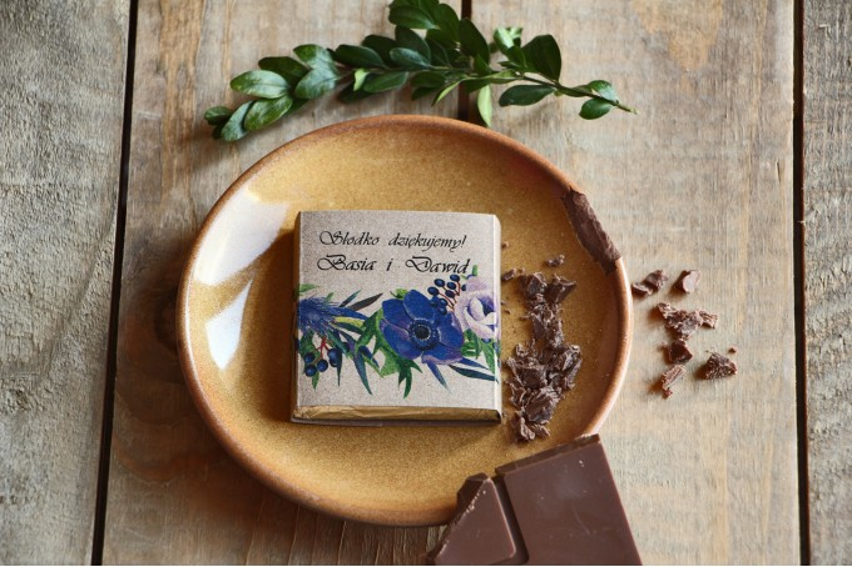 Podziękowanie dla gości weselnych w postaci mlecznej czekoladki, owijka z grafiką chabrowych anemonów oraz czarnego bzu