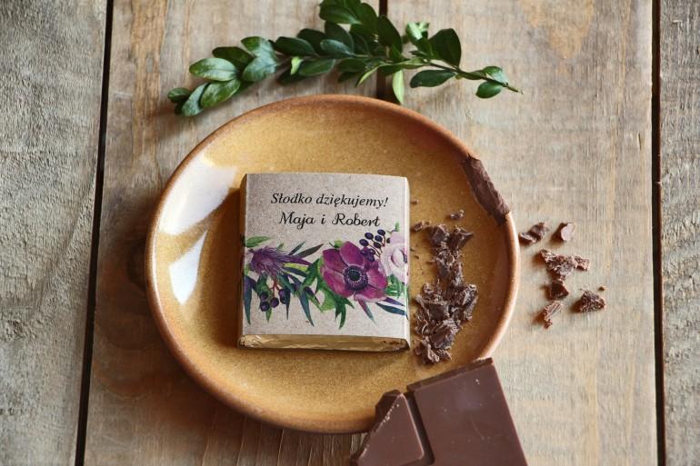 Podziękowanie dla gości weselnych w postaci mlecznej czekoladki, owijka z grafiką fioletowych anemonów oraz czarnego bzu