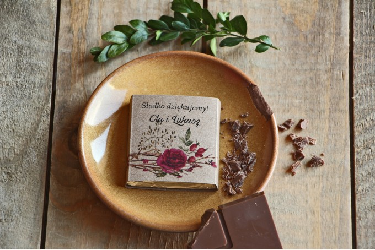 Podziękowanie dla gości weselnych w postaci mlecznej czekoladki, owijka z grafiką dzikiej róży.