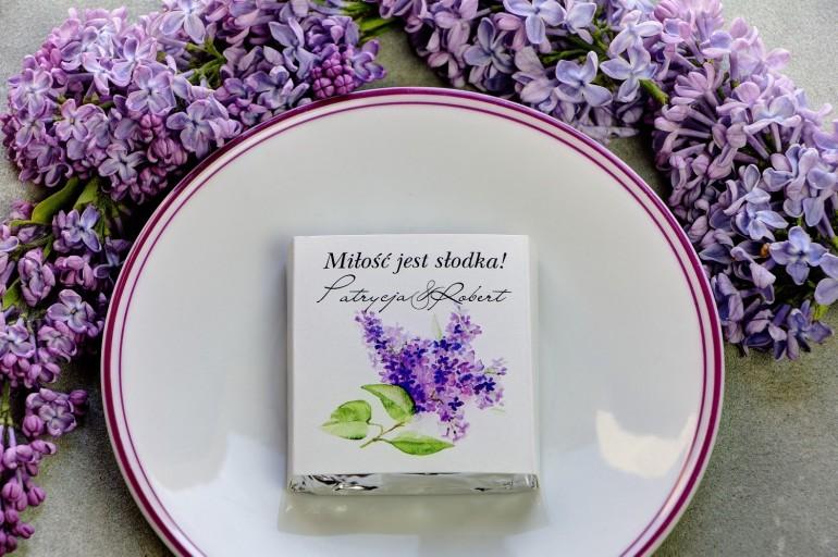 Podziękowanie dla gości weselnych w postaci mlecznej czekoladki, owijka z fioletowymi kwiatami bzu