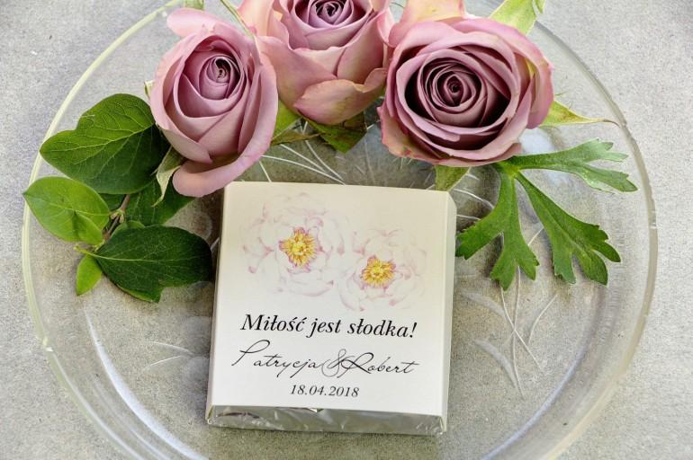 Podziękowanie dla gości weselnych w postaci mlecznej czekoladki, owijka z jasnoróżową peonią