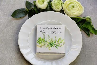 Podziękowanie dla gości weselnych w postaci mlecznej czekoladki, owijka z zieloną kompozycją połączoną w delikatny wianek