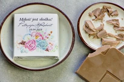 Podziękowanie dla gości weselnych w postaci mlecznej czekoladki, owijka w stylu boho z różowymi piwoniami oraz z piórkami