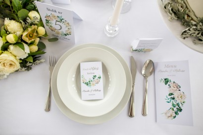 Podziękowanie dla gości w postaci nasion niezapominajki. Opakowanie z srebrnymi napisami oraz kremowymi piwoniami