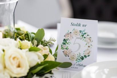 Numery stolików weselnych ze srebrzeniem. Wianek z kremowymi piwoniami oraz eukaliptusem