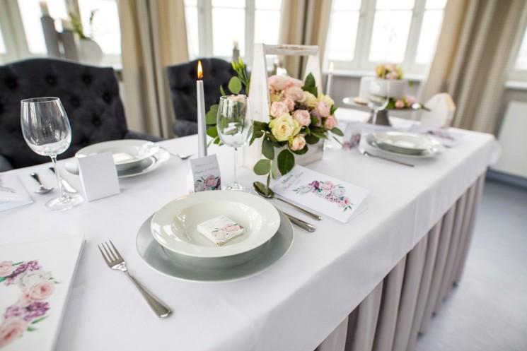 Stół weselny z zaproszeniami ślubnymi, dodatkami weselnymi. Białe i różowe piwonie oraz bez