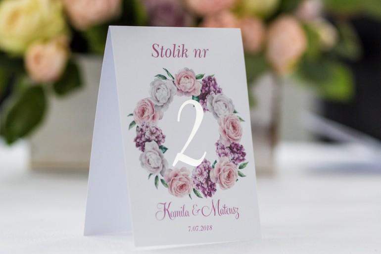 Numery stolików weselnych ze srebrzeniem. Wianek z białymi i różowymi piwoniami oraz kwiatami bzu