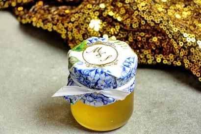 Słoiczek z miodem - słodkie podziękowanie dla gości weselnych. Kapturek ze złoconymi inicjałami. Błękitna hortensja.
