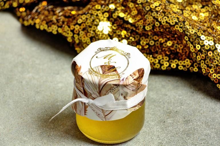 Słoiczek z miodem - słodkie podziękowanie dla gości weselnych. Kapturek ze złoconymi inicjałami. Delikatne piórka w stylu boho