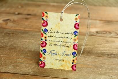 Ludowe Zawieszki na butelki weselne z wycinanką łowicką. Bogata gama kolorów podkreśla folklorystyczny charakter zawieszki.