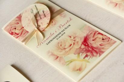 Kremowe zaproszenia ślubne z piwonią w pastelowym odcieniu jasnego różu. Całość przewiązana ozdobną przywieszką z wierszykiem.