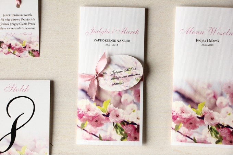 Zaproszenia ślubne z gałązką kwitnącej wiśni. Całość przewiązana ozdobną przywieszką z wierszykiem.