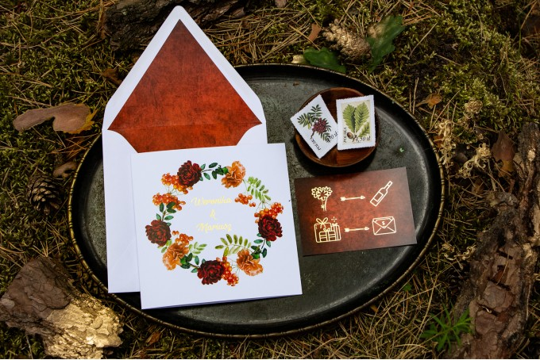 Jesienne zaproszenia ślubne z jarzębiną, bordowymi różami i pomarańczowymi goździkami