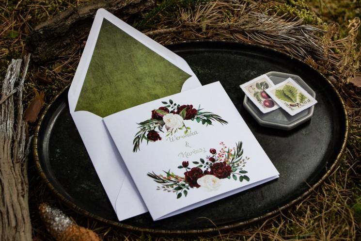 Zimowe zaproszenia ślubne z bordowymi piwoniami z dodatkiem bieli i zieleni. Całość uzupełnia biała koperta z wklejką