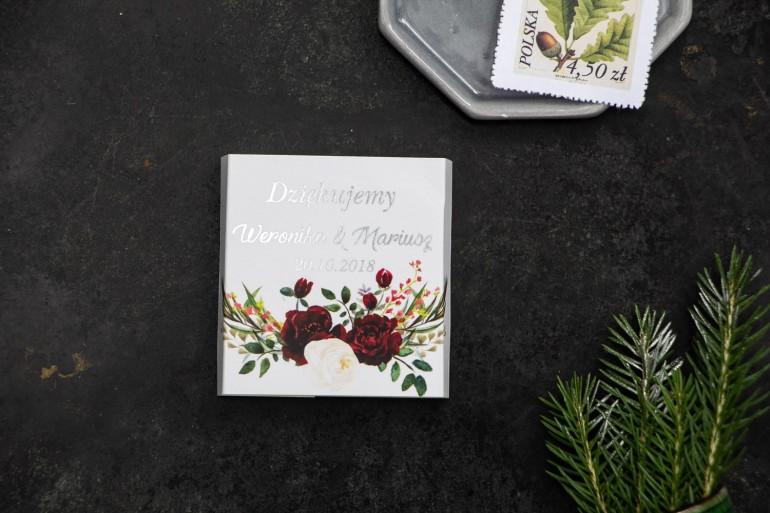 Podziękowanie dla gości weselnych w postaci czekoladki, owijka ze srebrnymi napisami oraz grafiką z bordowymi piwoniami