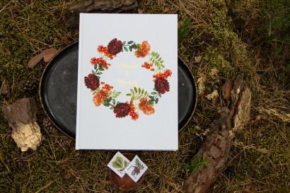 Weselna, ślubna Księga Gości ze złotymi napisami. Grafika z jarzębiną, bordowymi różami i pomarańczowymi goździkami