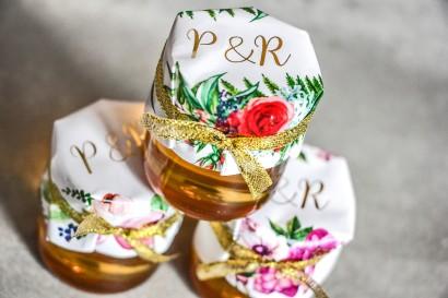 Słoiczek z miodem - słodkie podziękowanie dla gości weselnych. Kapturek ze złoconymi inicjałami z czerwonymi różami i paprocią.