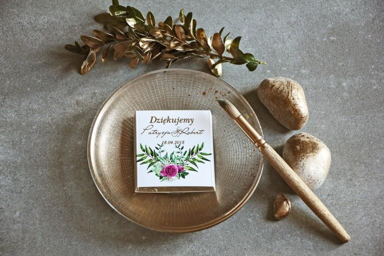 Podziękowanie dla gości weselnych w postaci mlecznej czekoladki, owijka ze złoconymi napisami oraz grafiką róż i gałązek