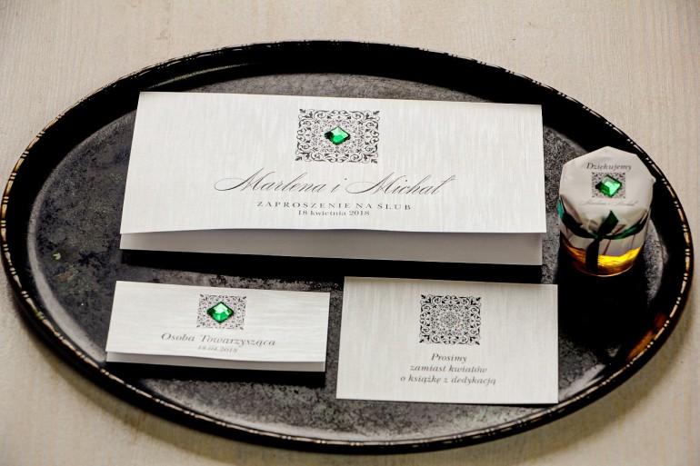 Srebrne zaproszenia ślubne z ozdobnym, szmaragdowym kamyczkiem. Całość wykonana na papierze jednostronnym perłowym.