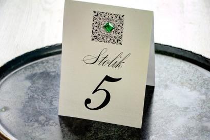 Srebrne numery stolików, na papierze jednostronnie perłowym z ornamentem oraz szmaragdowym kamykiem