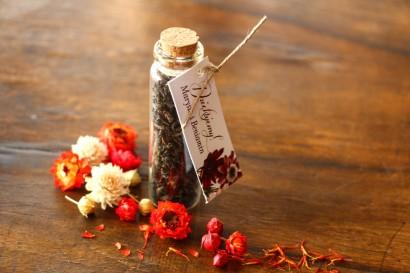 Podziękowania dla Gości w postaci buteleczek z herbatą, przywieszka z motywem bordowych i burgundowych stokrotek afrykańskich