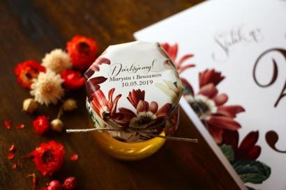 Słodkie podziękowania dla gości weselnych w postaci słoiczków z Miodem z motywem bordowych i burgundowych stokrotek afrykańskich