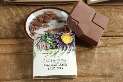 Podziękowanie dla gości weselnych w postaci mlecznej czekoladki, owijka z astrami w odcieniach fioletu oraz gałązkami paproci