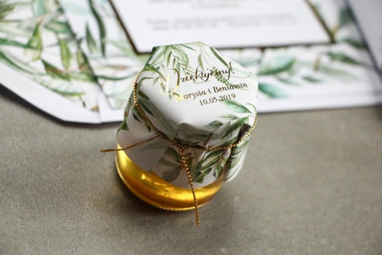 Słoiczek z miodem - słodkie podziękowanie dla gości weselnych. Kapturek ze złoconymi napisami oraz botanicznym motywem greenery
