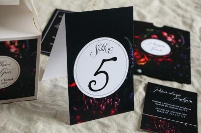 Numery stolików weselnych w botanicznym stylu. Czarna grafika przełamana bordowymi i burgundowymi kwiatami piwonii i róż