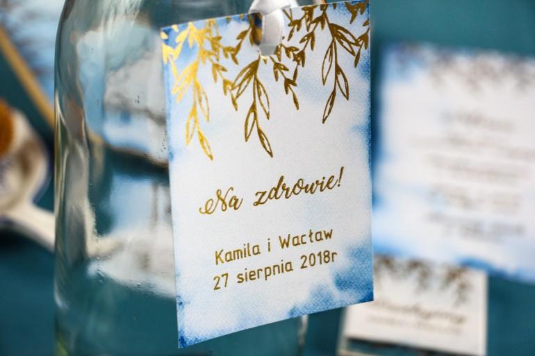 Niebieskie zawieszki na butelki weselne ze złoceniami.